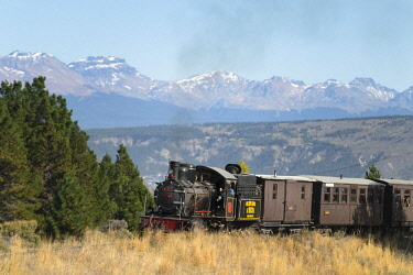 ARFEMR001024 Locomotive crossing Old Patagonian Express railway with mountain range in background, Esquel, Chubut, Argentina