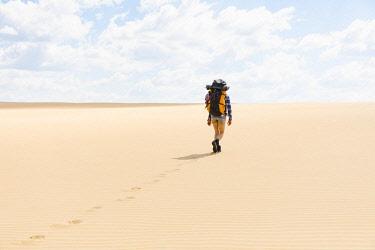 ARPEAN000640 Rear view of woman hiking on sandy beach in Great Sandy National Park, Noosa Heads, Queensland, Australia
