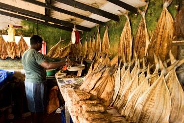 ARHARO010277 Man working at roadside shack with dry fish, Sri Lanka