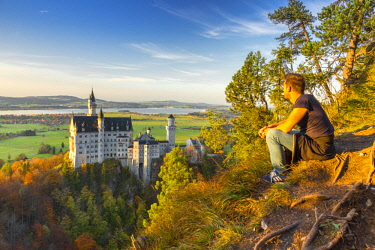 CLKAB74671 Resting and admiring panorama near Neuschwanstein Castle in Autumn at sunset. Schwangau, Fussen, Southwest Bavaria, Bavaria, Germany, Europe