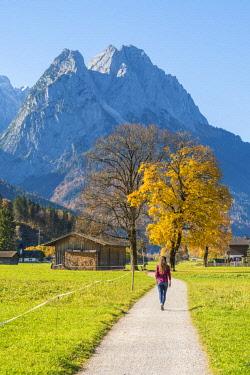 CLKAC74062 Garmisch Partenkirchen, Bavaria, Germany, Europe. A young woman walking on a footpath in autumn