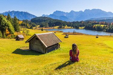 CLKAC74070 Gerold, Garmisch Partenkirchen, Bavaria, Germany, Europe. Young woman relaxing on a meadow near lake Geroldsee, Karwendel range in the background