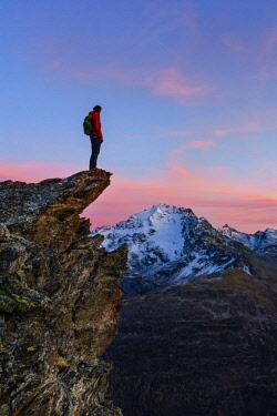 CLKGM73210 An hiker on a rock with a panoramic view at sunset. Valdidentro, Valtellina, Lombardy, Italy