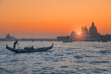 CLKMG74988 Gondola on the Grand Canal at sunset with Basilica of Saint Mary of Health in background, Punta della Dogana, Venice, Veneto, Italy