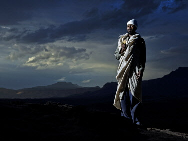ETH3404AW Africa, Ethiopia, Tigray. A priest stands holding his Orthodox cross against a dramatic stormy backdrop