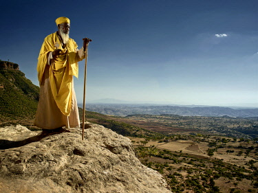 ETH3421AW Africa, Ethiopia, Tigray.  Head monk in yellow robes stands with his Orthodox cross and staff looking out overthe highlands