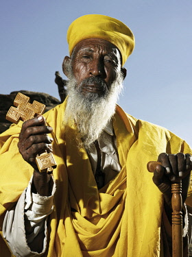 ETH3422AW Africa, Ethiopia, Tigray. Head monk in yellow robes stands with his Orthodox cross and staff lo