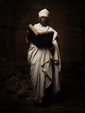 ETH3427AW Africa, Ethiopia, Tigray.  A priest reads his bible inside one of the Orthodox rock hewn churches