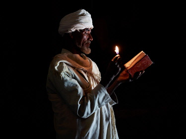 ETH3428AW Tigraen priest reads his bible by the light of a candle