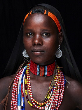 ETH3432AW Africa, Ethiopia, Omo Delta.  A young woman of the Arbore tribe shows off her elaborate beaded necklaces and adornments