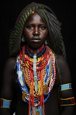 ETH3435AW Africa, Ethiopia, Omo Delta.  A young woman of the Arbore tribe shows off her elaborate beaded necklaces and adornments