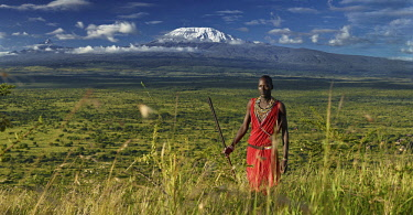 KEN10466AW Africa, Kenya, Amboseli.  Maasai warrior with spear standing on hillside with Mt Kilimanjaro behind