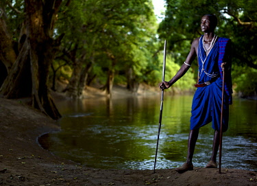 KEN10477AW Africa, Kenya.  A Maasai warrior in a blue shuka stands with his spear beside a remote pool of water.