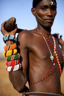 KEN10490AW Africa, Kenya, Samburu.  A Samburu moran or warrior shows off his beaded bracelets.