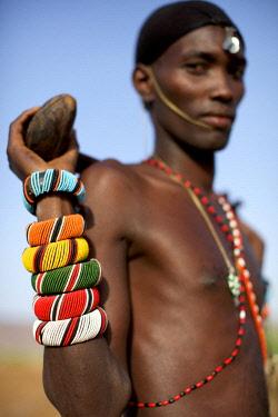 KEN10491AW Africa, Kenya, Samburu.  A Samburu moran or warrior shows off his beaded bracelets.