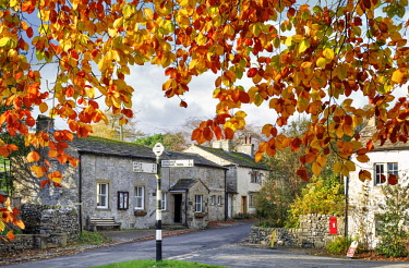 ENG15255AW England, North Yorkshire, Malham. A view of the village framed by autumn leaves.
