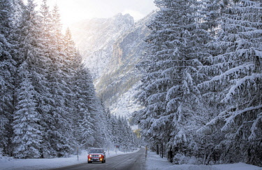 ITA11445AW Scenic route with red car and snowy winter landscape, Dolomites Alps, Italy