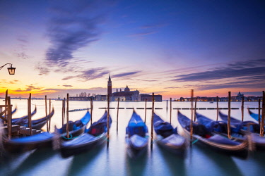 ITA11457 Italy.Veneto.Venice. Gondolas moored at the bacino di San Marco with the church of San Giorgio Maggiore in the background.