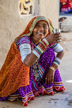 IND8399AW Hodka, Bhuj, Gujarat, India. Indian woman seated drinking water and  is wearing Banni embroidered clothes, along with chain-stitched mirror