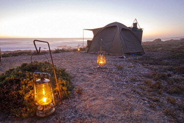 SAF7546 Oil lamps lighting the path to a tent at Namaqua Flower Beach Camp, Namaqua National Park, Northern Cape, South Africa