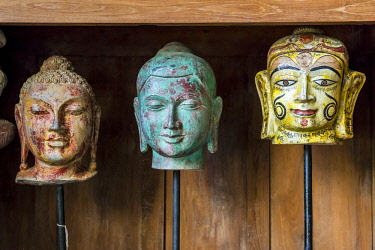 IND8487AW Jaipur, Rajasthan, India. Carved heads of Buddah fore sale in antique store.