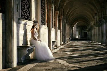 HMS3093824 Italy, Veneto, Venice, listed as World Heritage by UNESCO, Saint Mark's Square (Piazza San Marco), Doge's Palace arcade and columns (Palazzo Ducale), woman in a wedding dress with a carnival mask