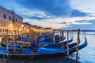 ITA11792AW Venice, Veneto, Italy. Gondolas moored on the waterfront of St Mark's basin at dusk.