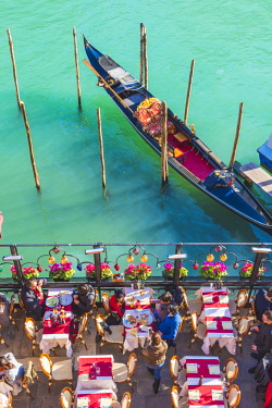 Venice, Veneto, Italy. Tourists eating out on the riverside of the Grand Canal.