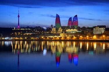 HMS2193855 Azerbaijan, Baku, Baku Bulvar (Boulevard), city illuminated at dusk reflected in the Caspian sea, the Flame Towers with the colours of the national flag and the TV Tower