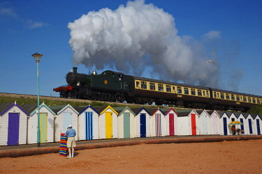 HMS3121176 United Kingdom, Devon, children, old train Torbay express spitting a cloud of smoke above colorful beach cabins