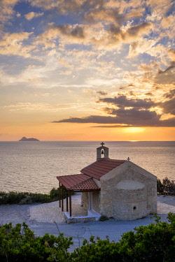 HMS3113619 Greece, Crete, Heraklion district, surroundings of Matala, Messara bay at sunset, Agios Panteleimona church overlooks Kommos (or Komos) beach