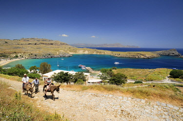 Greece, Dodecanese Islands, Rhodes island, Lindos, two people on two mules going to the Acropolis