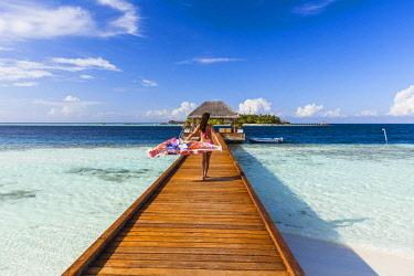 MIV0383AW Woman with sarong walking on jetty, Maldives (MR)