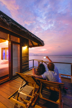 MIV0388AW Couple watching sunset from overwater bungalow, Maldives (MR)