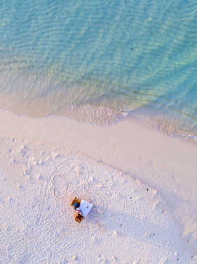 MIV0419AW Aerial drone view of adult couple eating dinner on a sandy beach at sunset, Maldives (MR)