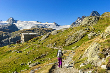 HMS2456873 Italy, Valle d'Aosta, La Thuile, hiker arriving at the Deffeyes refuge with behind the Ruitor Glacier