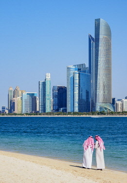 UAE0671AW Two men wearing thawb on the beach and City Center Skyline, Abu Dhabi, United Arab Emirates