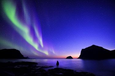 HMS2399172 Norway, Nordland, Lofoten islands, Vestvagoy island, Vik beach, silhouette of a woman and northern lights (aurora borealis)