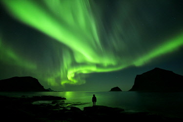 HMS2399173 Norway, Nordland, Lofoten islands, Vestvagoy island, Vik beach, silhouette of a woman and northern lights (aurora borealis)