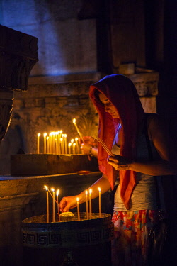 ISR0335 Israel, Jerusalem. A young Orthodox woman placing candles in the Greek Orthodox part of the Church of the Holy Sepulchre.