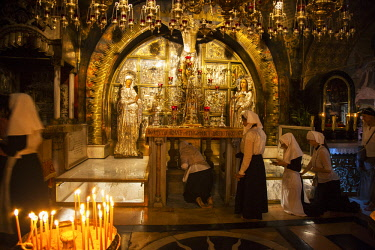 ISR0330 Israel, Jerusalem. Eastern Orthodox nuns at the chapel believed to be the place of the Golgotha or the place of crucifixion of Jesus Christ in the Greek Orthodox part of the Church of the Holy Sepulch...