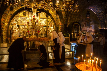 ISR0329 Israel, Jerusalem. Eastern Orthodox nuns at the chapel believed to be the place of the Golgotha or the place of crucifixion of Jesus Christ in the Greek Orthodox part of the Church of the Holy Sepulch...