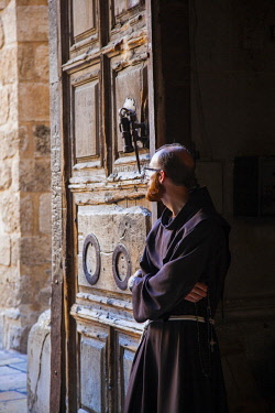 ISR0319 Israel, Jerusalem. A Franciscan monk at the main door of one of the most important Catholic Churches in the World, the Church of the Holy Sepulchre.