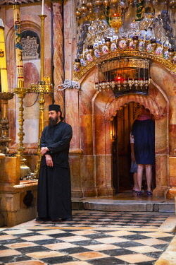ISR0312 Israel, Jerusalem. A Greek Orthodox monk guarding the entrance to what is believed to be the tomb of Christ from where he also ressurected at one of the most important Catholic Churches in the World,...