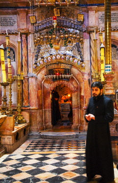 ISR0311 Israel, Jerusalem. An Armenian Orthodox monk guarding the entrance to what is believed to be the tomb of Christ from where he also ressurected at one of the most important Catholic Churches in the Wor...