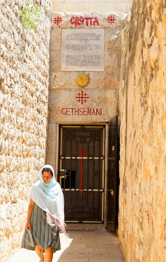 ISR0298 Israel, Jerusalem. A woman exiting the grotto which is believed to be the place where Jesus of Nazareth prayed in the Gethsemani Garden of Olives before being betrayed.