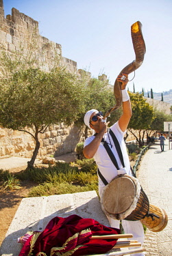 ISR0283 Israel, Jerusalem. Young musician playing the traditional Jewish instrument named shofar at the walls of the old city of Jerusalem. This is an ancient musical horn typically made from a ram s horn usu...