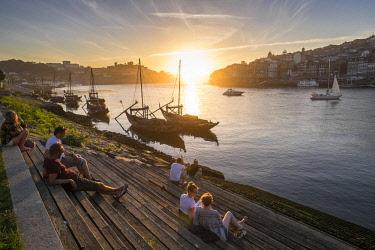 HMS2255141 Portugal, North region, Vila Nova de Gaia, sunset on Douro river, the historic center of Porto listed as World Heritage by UNESCO, in background