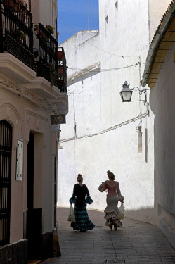 HMS3085610 Spain, Andalusia, Cordoba, mezquita, listed as World Heritage by UNESCO, old town, two women in traditional andalusian dress in chinese shadow standing out againts the white wall of a lane