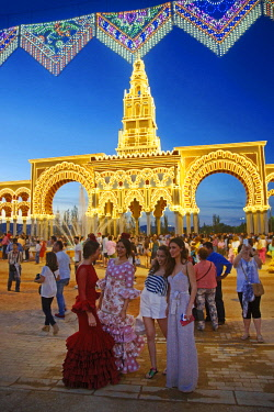 HMS3085614 Spain, Andalusia, Cordoba, girls in andalusian traditional dress in front of the illuminated monumental entrance of the feria de Nuestra senora de la salud, at night